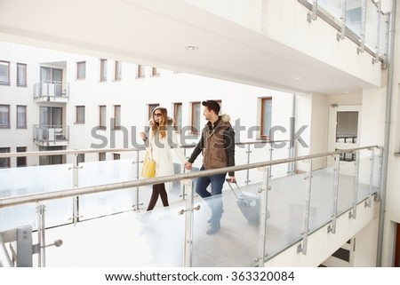 Young couple leaving apartment house with small luggage hand in hand. - stock photo