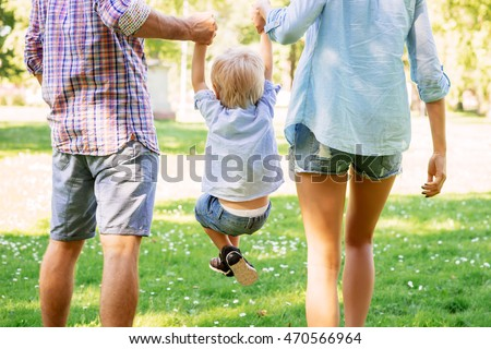 Young couple lifting their son while walking in the park.