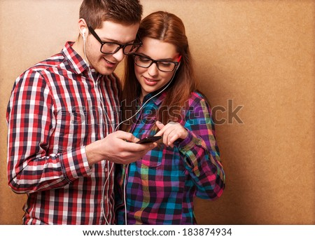 Young couple listening music together. Hipster style. - stock photo