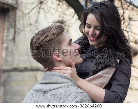 Young couple look at each other on the street near the tree - stock photo