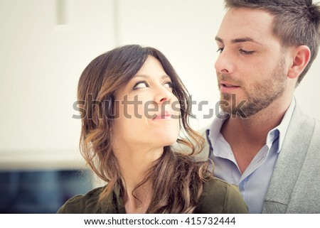 young couple look each other in the kitchen