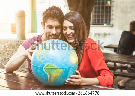 Young couple look the world map to decide the next trip - stock photo