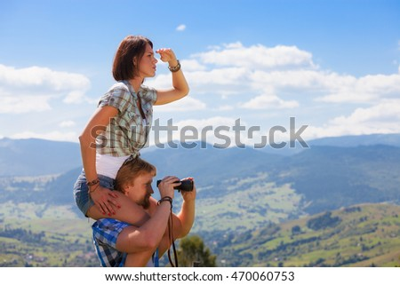 Young couple looking around mountain countryside summer view