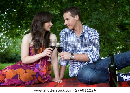 Young couple looking at each other and toasting wine in park - stock photo