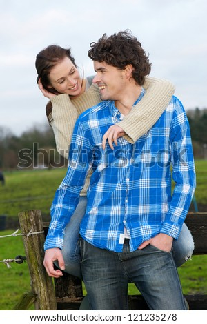 Young couple looking at each other outdoors. Handsome man and beautiful girl are smiling and showing togetherness - stock photo