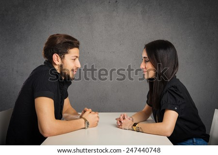Young couple looking at each other studio portrait against grunge background. - stock photo
