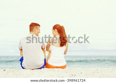 Young couple looking at each other while sitting on beach - stock photo
