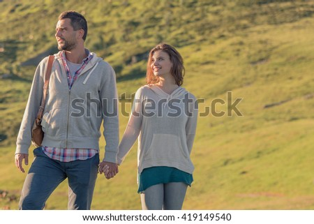 Young couple looking at panorama on sunset in nature