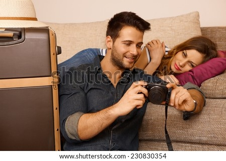 Young couple looking at photos taken on holiday before leaving. - stock photo