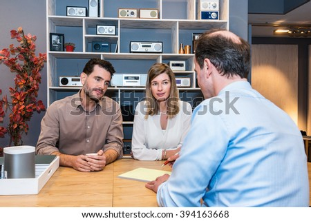 Young couple looking at salesman making sale receipt in electronics store - stock photo