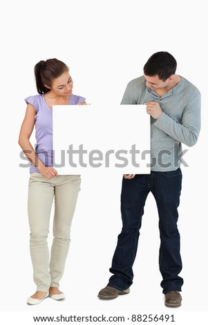 Young couple looking at sign they are holding against a white background - stock photo
