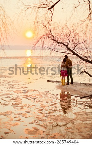 young couple looking at sunset - stock photo