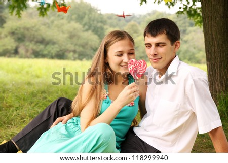 young couple looking at the big candy - stock photo