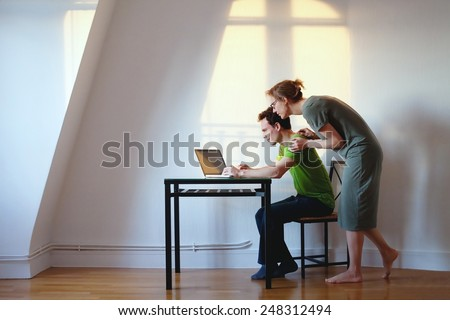 young couple looking at the laptop at their home in bright interior - stock photo