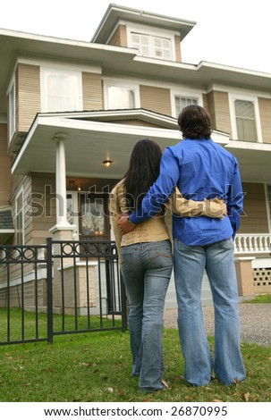 young couple looking at their house. photograph taken from back - stock photo