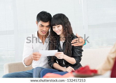 Young couple looking at ticket indoors