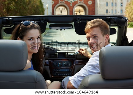 Young couple, looking back, sits in a cabriolet against building with two arches, girl is on a driver seat. - stock photo