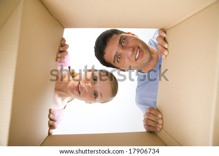 Young couple looking into cardboard box. They look like surprised. Looking at camera. Low angle view. - stock photo