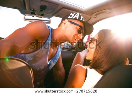 Young couple looking into each other's eyes.Emotional people,Romantic hipster couple sitting on hood of their car enjoying the moment,outdoors with copy space.Young couple in love on a road trip.caps  - stock photo