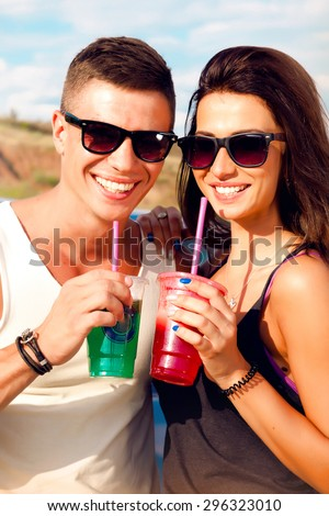 Young couple looking into each other's eyes.Romantic young couple on hood of their car enjoying the moment,outdoors with copy space.Young couple in love on a road trip.Couple drinking coffee,drinks - stock photo