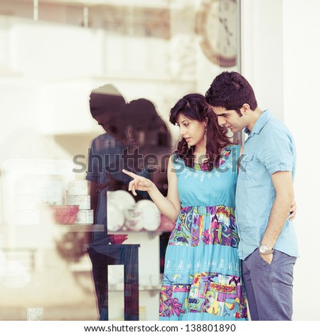 young couple looking into shop window and discussing - stock photo