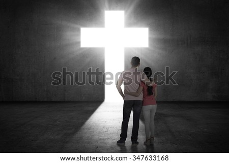 Young couple looking the shining cross on the wall. Religious concept