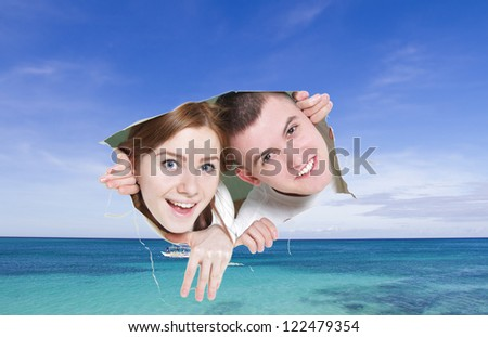 young couple looking though hole at tropical sea - concept shot - stock photo