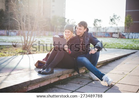 young couple lovers authentic using tablet connected online in the city - stock photo