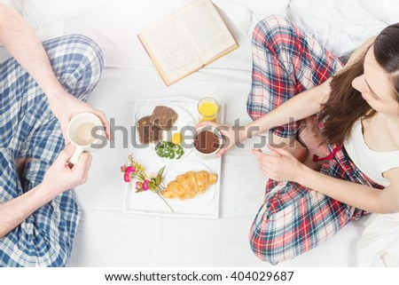 Young couple lovers romantic relationship having breakfast together in white bed. Eating loving and reading. Top view