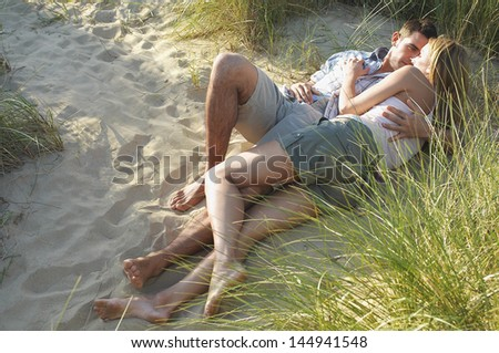 Young couple lying and embracing in secluded spot at beach - stock photo