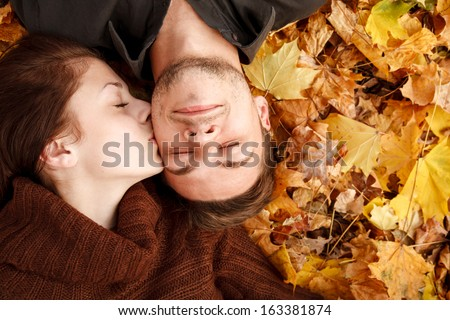 young couple lying down on autumn leaves eyes closed she kissing him - stock photo