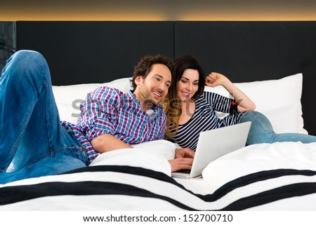 Young Couple lying in the bed of a hotel room, they are on vacation and using the wifi in the room for internet with the computer