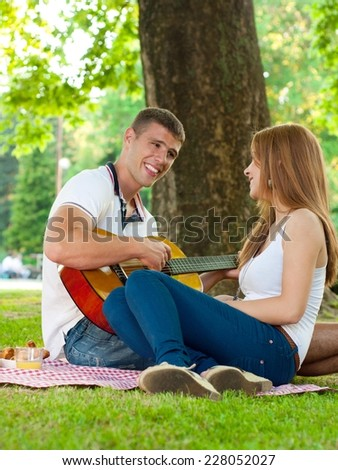 Young couple lying in the park on a summer day. Man is playing a guitar.