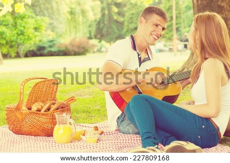 Young couple lying in the park on a summer day. Picnic basket in the background. Man is playing a guitar. - stock photo