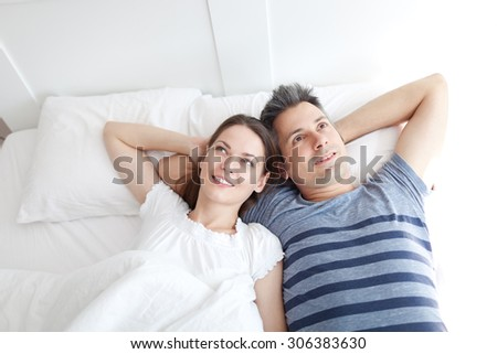 Young couple lying on bed, relaxing - stock photo