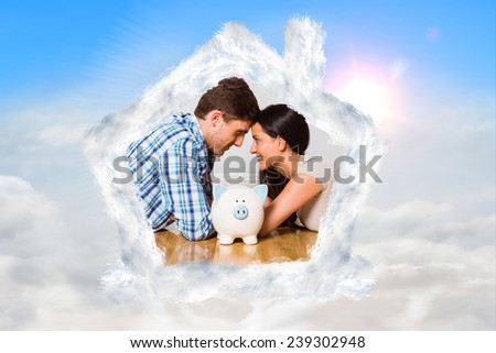 Young couple lying on floor smiling with piggy bank against blue sky with white clouds - stock photo