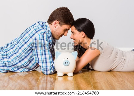 Young couple lying on floor smiling with piggy bank at home - stock photo