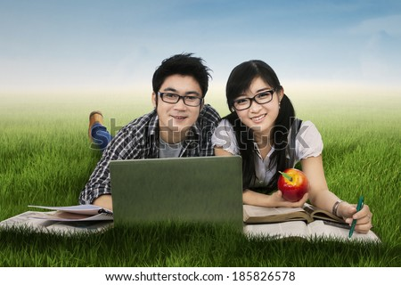 Young couple lying on grass while studying with laptop - stock photo