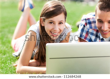 Young couple lying on grass with laptop - stock photo