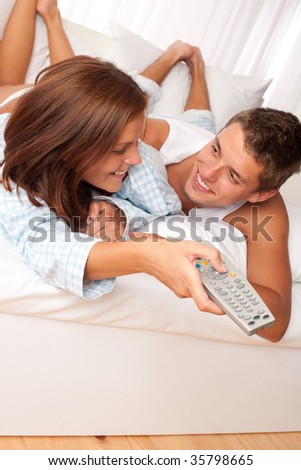 Young couple lying on sofa watching television