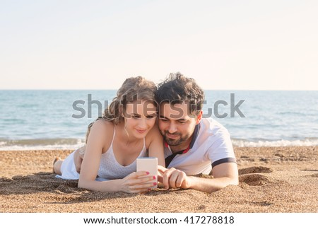 Young couple lying on the beach, using smart phone - stock photo