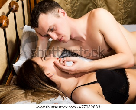 young couple lying on the bed in the hotel. the man leaned over young woman, his hand stroking her cheek