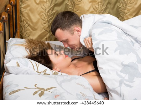 young couple lying on the bed in the hotel. the man leaned over young woman, his hand stroking her cheek - stock photo