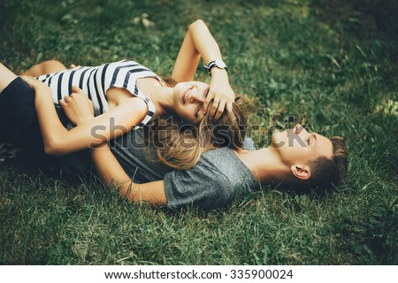 Young couple lying on the grass on sunny day - stock photo