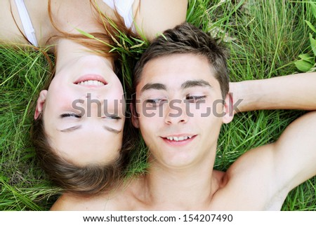 Young couple lying on the grass, top view - stock photo