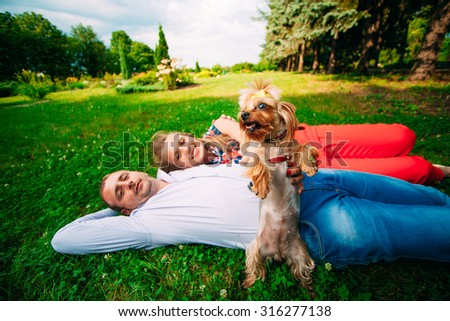 Young couple lying on the grass with a small dog - stock photo
