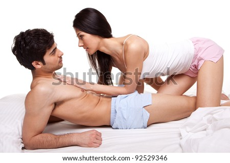 Young Couple lying on top of a bed and staring intently into each others eyes with love. - stock photo