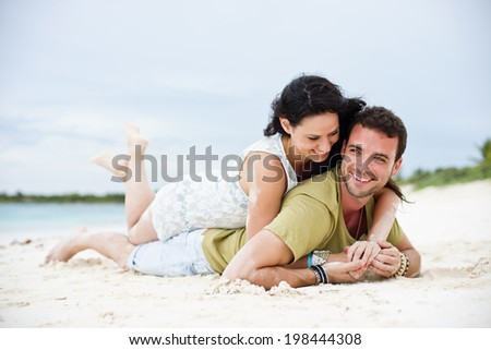 Young couple lying together in a tropical beach - stock photo