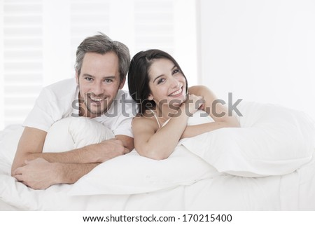 Young couple lying together in bed in the bedroom - stock photo