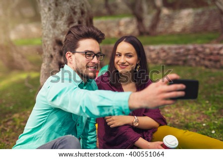 Young couple make selfi under the olive tree